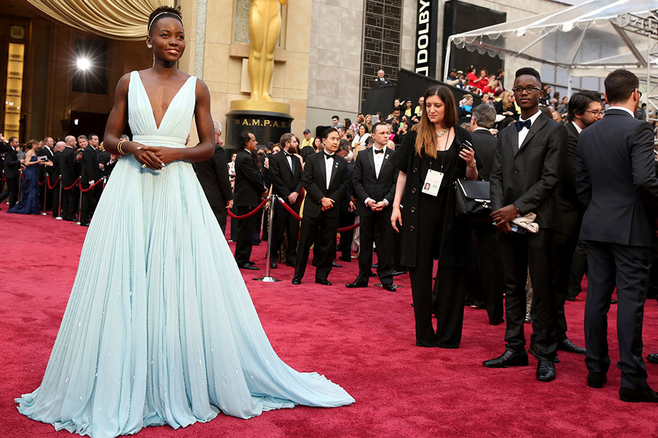 "This March 2, 2014 file photo shows Lupita Nyong'o in a pale blue Prada dress at the Oscars in Los Angeles. What happens to the duds after a big awards night can be a peculiar affair that depends on the relationship a celebrity has with a designer. Nyong'o, who won the Oscar for best supporting actress for ""12 Years a Slave,"" was able to keep her gown"