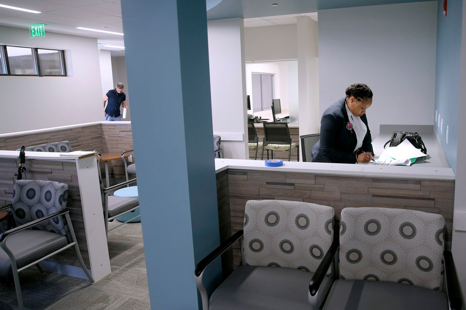 In this Oct. 2, 2019, file photo, Anita Murphy, a Planned Parenthood executive, does paperwork in the waiting room during a media tour of the new Fairview Heights, Ill., facility prior to open that month. Illinois is among several states picking up the tab in 2020 for family planning services at clinics run by Planned Parenthood, which quit participating in the federal funding program in 2019
