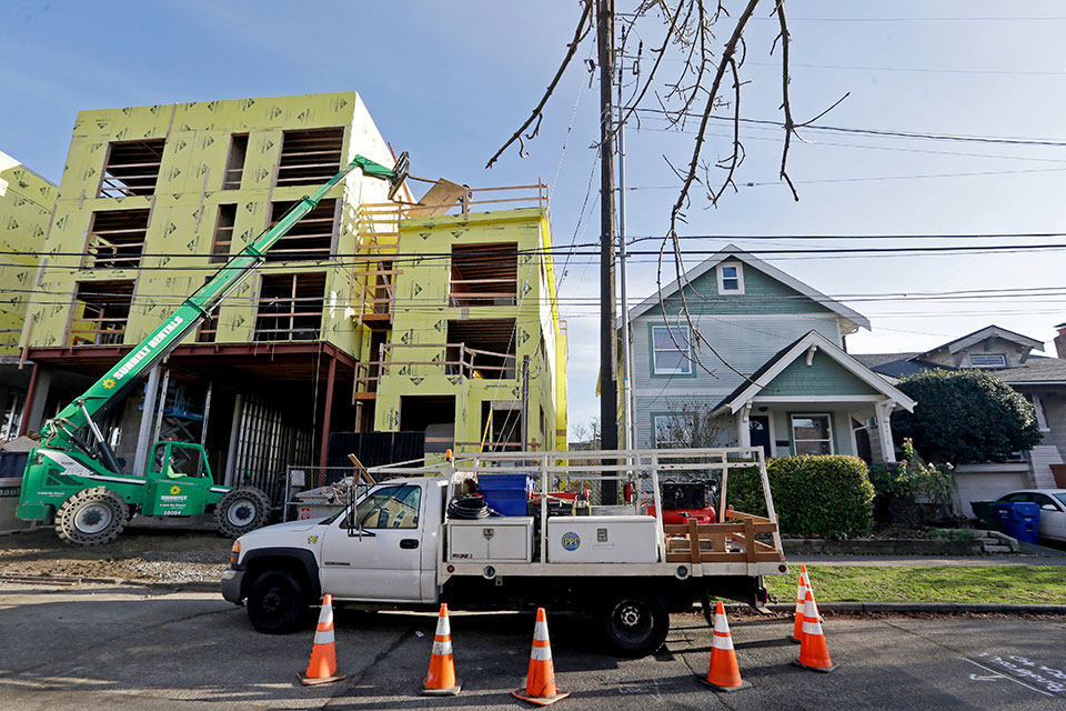 In this Dec. 13, 2017 file photo, a four-story mixed-use building is under construction adjacent to an older, single-family home in Seattle. A massive influx of new residents and an ensuing housing crunch has led to skyrocketing rents. On Monday, Feb. 10, 2020, the Seattle City Council unanimously approved a ban on evictions during December, January and February.
