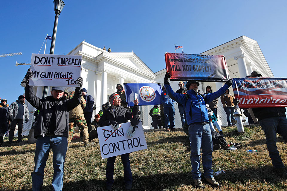 This Monday an. 20, 2020 file photo shows pro gun demonstrators holding signs in front of the Virginia State Capitol in Richmond, Va. In a state once synonymous with the Old South, Democrats are using their newfound legislative control to refashion Virginia as the region's progressive leader on racial, social and economic issues
