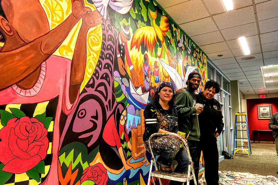 From left to right: Artists Addie Boswell and Antwoine Thomas with Fire Chief Sara Boone in front of the new mural