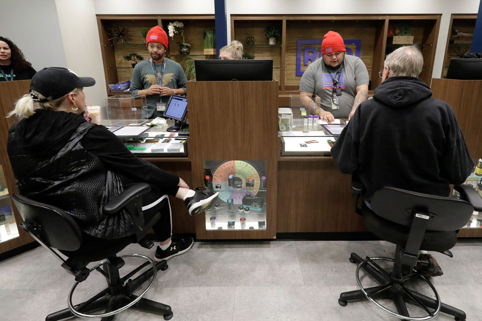 In this Thursday, Dec. 26, 2019 photo, registered medical marijuana patients talk with staff members at the Rise cannabis store in Mundelein, Ill. Starting Jan. 1, 2020, Illinois will join Michigan as the only Midwestern states broadly allowing the sale and use of marijuana