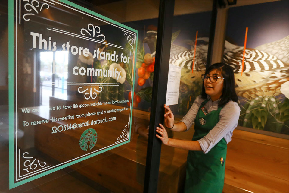 In this Wednesday, Jan. 15, 2020, photo, Belith Ariza, a barista trainer at Starbucks, opens the doors to the community meeting space at a local Starbucks Community Store, in Phoenix. The Seattle-based company plans to open or remodel 85 stores by 2025 in rural and urban communities across the U.S.