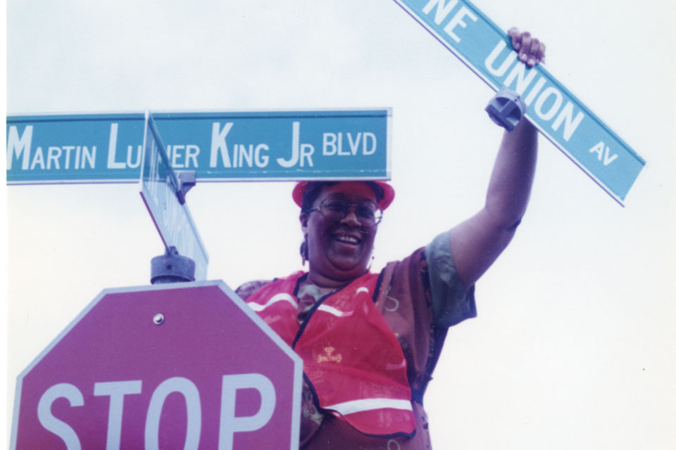 Carolyn Leonard removing Union Avenue street sign at corner of NE Martin Luther King, Blvd. and NE Simpson St. In the 1980s, when local citizens started organizing to change the name from Union Avenue, the struggle was so bitter that The Skanner publisher Bernie Foster–who helped lead to campaign –received death threats.
