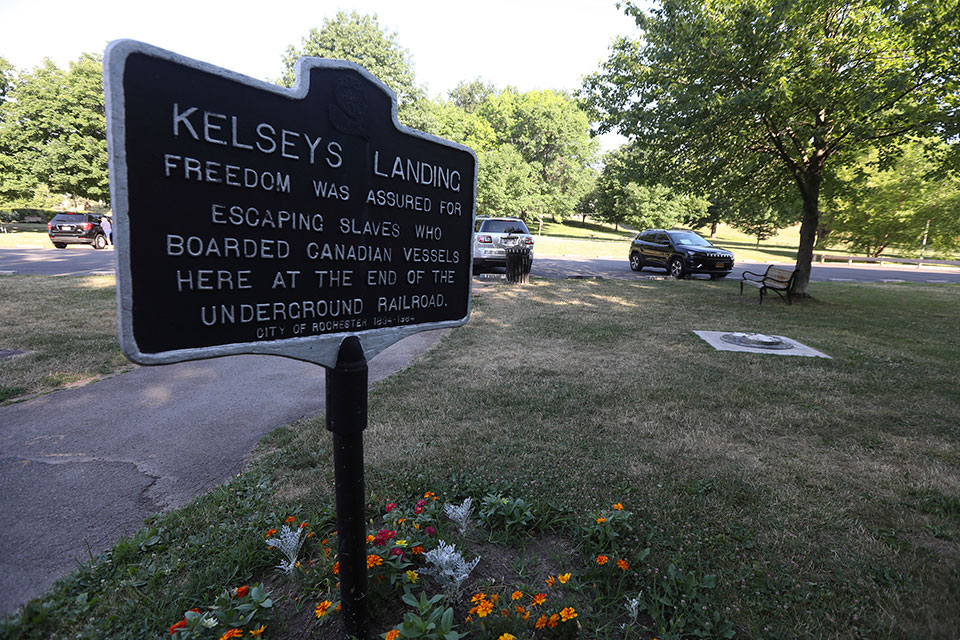 A sign marking a historic Underground Railroad spot sits near the base of a statue of Frederick Douglass which is all that remains, Monday, July 6, 2020 in Rochester, N.Y., after it was found vandalized in Maplewood Park. Police say the statue of Douglass was taken from Maplewood Park and placed near the Genesee River gorge on Sunday. This site includes Kelsey's Landing, a part of the Underground Railroad, where Douglass, Harriet Tubman and others helped slaves get to freedom via the Genesee River located below adjacent gorge. (Tina MacIntyre-Yee/Rochester Dem via AP)