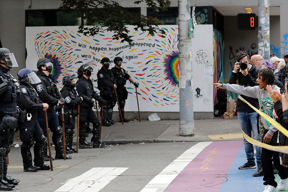 Protesters stand behind police tape as police officers look on Wednesday, July 1, 2020, in Seattle, where streets had been blocked off in an area demonstrators had occupied for weeks. Seattle police showed up in force earlier in the day at the