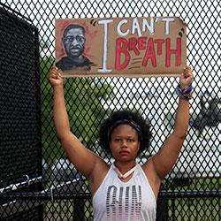 A demonstrator holds a sign as people protest Friday, June 5, 2020, near the White House in Washington