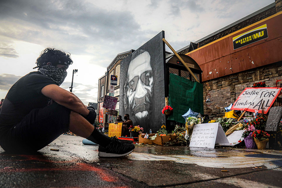 "After a new mural, center, of George Floyd is added to a growing memorial of tributes, Trevor Rodriquez sits alone at the spot where Floyd died while in police custody, Tuesday June 2, 2020, in Minneapolis, Minn. ""I have been out every single night protesting peacefully, just trying to support everything,"" said Rodriquez. ""I didn't want to come here just on a rush, so I had to just take a moment to pay my respect."" (AP Photo/Bebeto Matthews)"