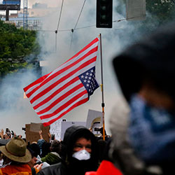 Smoke from a flashbang grenade rises on Pine Street east of Westlake Park during a protest, Saturday, May 30, 2020 in Seattle.