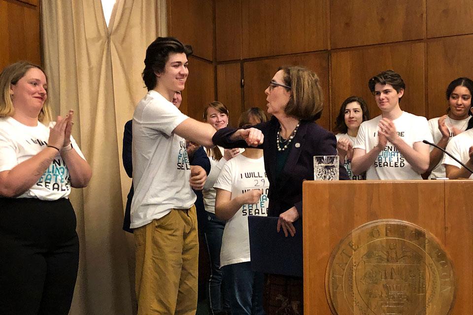 Oregon Gov. Kate brown elbow-bumps student Charlie Abrams at a ceremony on Tuesday, March 10, 2020, where she signed a sweeping executive order for the state to reduce carbon emissions to combat global warming. Amid a spreading coronavirus outbreak, many people are no longer shaking hands and are coming up with alternatives, like the elbow bump. (AP Photo/Andrew Selsky)