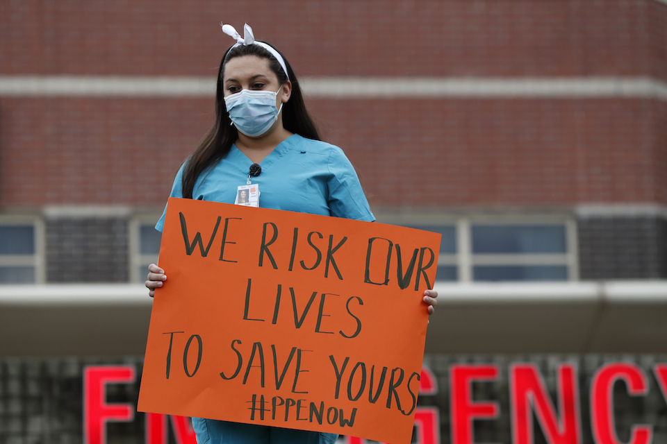 A nurse demonstrates outside the emergency entrance at Jacobi Medical Center in the Bronx borough of New York, Saturday, March 28, 2020, demanding more personal protective equipment for medical staff treating coronavirus patients. A member of the New York nursing community died earlier this week while treating coronavirus patients at another New York hospital. The city leads the nation in the number of COVID-19 cases, and the United States currently has the most cases in the world, according to the World Health Organization. (AP Photo/Kathy Willens)