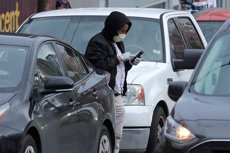 A man wears a mask as he checks his phone, Tuesday, March 24, 2020, in Seattle's Capitol Hill neighborhood. Washington Gov. Jay Inslee on Monday, March 23, 2020, ordered nonessential businesses to close and the state's more than 7 million residents to stay home in efforts to slow the spread of the new coronavirus. The new coronavirus causes mild or moderate symptoms for most people, but for some, especially older adults and people with existing health problems, it can cause more severe illness or death. (AP Photo/Ted S. Warren)