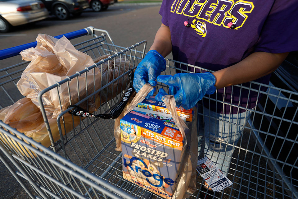 A gloved shopper prepares to load up her purchases in the Kroger parking lot in northeast Jackson, Miss., Wednesday, April 8, 2020. (AP Photo/Rogelio V. Solis)