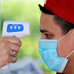 Edwin Hernandez has his temperature checked as part of a screening for coronavirus symptoms at a portable testing site for maritime workers at Fisherman's Terminal Wednesday, May 27, 2020, in Seattle.