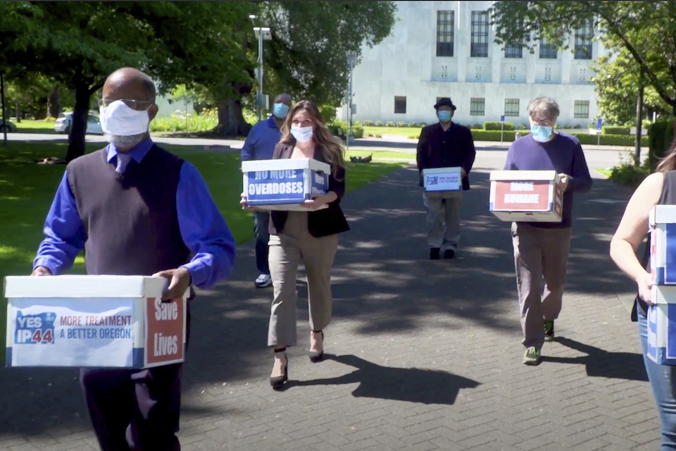"volunteers delivering boxes containing signed petitions in favor of the measure to the Oregon Secretary of State's office in Salem on June 26, 2020. In what would be a first in the U.S., possession of small amounts of heroin, cocaine, LSD and other hard drugs could be decriminalized in Oregon under a ballot measure that voters are deciding on in Tuesday's election. Oregon's Measure 110 is one of the most watched referendums in the state because it would drastically change how the justice system treats people with amounts of the drugs for their personal use. Instead of going to trial and facing possible jail time, people caught with the drugs would have the option of paying $100 fines or attending new ""addiction recovery centers."" (Yes on Measure 110 Campaign via AP)"