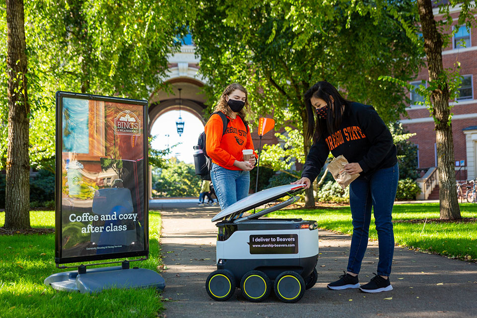 Starship Technologies has brought food delivery robots to the Oregon State University campus. Here, OSU students Maria Duong and Isabel Griffin receive a delivery. Photos by Blake Brown, UHDS marketing manager. Date: Oct. 18, 2020.