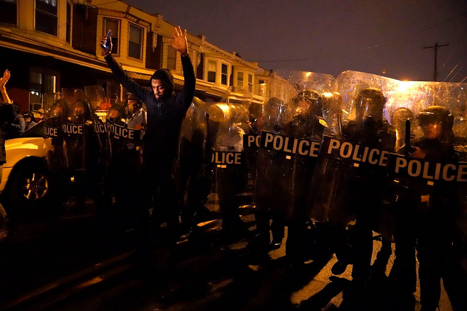 Sharif Proctor lifts his hands up in front of the police line during a protest in response to the police shooting of Walter Wallace Jr., Monday, Oct. 26, 2020, in Philadelphia. Police officers fatally shot the 27-year-old Black man during a confrontation Monday afternoon in West Philadelphia that quickly raised tensions in the neighborhood. (Jessica Griffin/The Philadelphia Inquirer via AP)