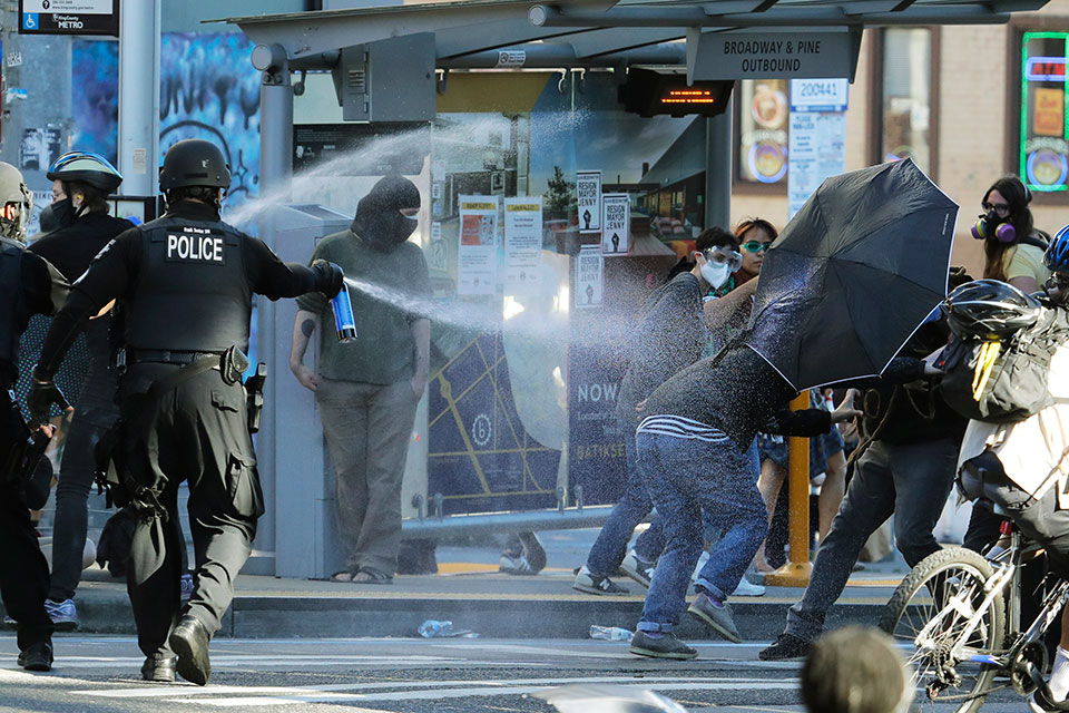 In this July 25, 2020, file photo, police pepper spray protesters, near Seattle Central College in Seattle, during a march and protest in support of Black Lives Matter. The Office of Police Accountability, an independent agency tasked with investigating police misconduct, said on Friday, Oct. 23, 2020, that in other incidents than the one pictured here, a Seattle police officer who slammed a protester's head to the ground, another who punched a demonstrator in the head a half dozen times and a third officer who put his knee on the necks of two looting suspects violated policies against using excessive force. (AP Photo/Ted S. Warren, File)