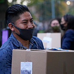 A man smiles beneath his protective face mask after receiving a box of donated food intended residents of the Corona neighborhood of the Queens borough of New York, Tuesday, Oct. 27, 2020.