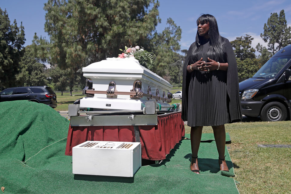 In this July 21, 2020, file photo, Candy Boyd, owner of Boyd Funeral Home, speaks to family members at an interment for Lydia Nunez, who died from COVID-19, at the Rose Hills Cemetery in Whittier, Calif. When people began dying from the coronavirus in the United States, for a few weeks, Boyd declined to receive the remains of such patients. Boyd feels that President Donald Trump is trying to downplay the virus. (AP Photo/Marcio Jose Sanchez, File)