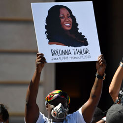 Signs are held up showing Breonna Taylor during a rally in her honor on the steps of the Kentucky State Capitol in Frankfort, Ky., Thursday, June 25, 2020. The city of Louisville will pay several million dollars to the mother of Breonna Taylor and install police reforms as part of a settlement of a lawsuit from Taylor's family, The Associated Press has learned. (AP Photo/Timothy D. Easley, File)