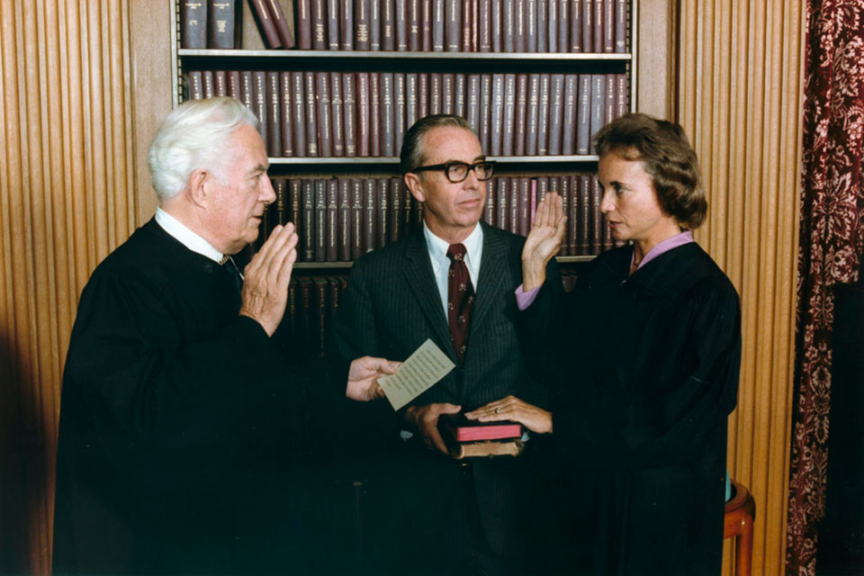 Sandra Day O'Connor is being sworn in a Supreme Court Justice by Chief Justice Warren Burger, as her husband John O'Connor looks on, 09/25/1981 (US National Archives)