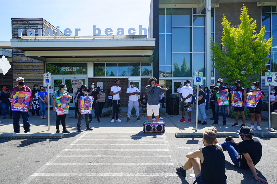 Dominique Harris, a Community Ambassador with Community Passageways, says a few words about the success of alternatives to incarcerating youth during a stop at the Rainier Beach Community Center, in City Council District 2 during a Labor Day Caravan and protest asking the City Council to override Mayor Durkan's veto of the City Council's recent vote to reduce funding to the Seattle Police Department's (SPD) 2020 budget. The caravan of 3 dozen cars drove through all 7 city council districts, stopping in each to hear from community members who support the veto. Seattle will reduce the police department's budget and reallocate some money to community programs after the City Council voted Tuesday, Sept. 22, 2020, to override Mayor Jenny Durkan's veto of adjustments to this year's budget. (photo by Susan Fried)