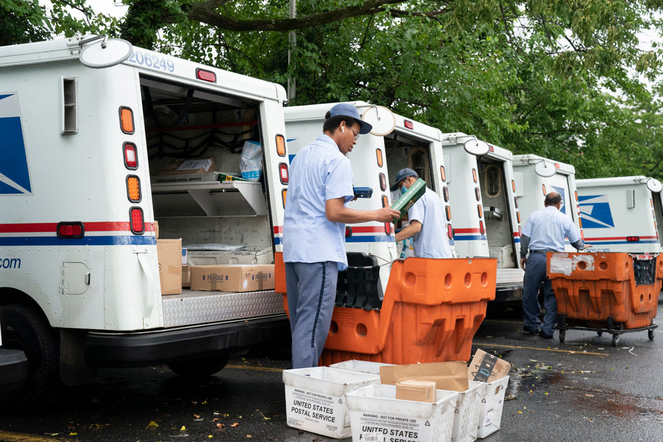 In this July 31, 2020, file photo, letter carriers load mail trucks for deliveries at a U.S. Postal Service facility in McLean, Va. A U.S. judge on Thursday, Sept. 17, 2020, blocked controversial Postal Service changes that have slowed mail nationwide. The judge called them