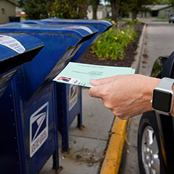In this Tuesday, Aug. 18, 2020, file photo, a person drops applications for mail-in-ballots into a mail box in Omaha, Neb.