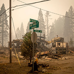Land and property at an intersection is scorched, Tuesday, Sept. 15, 2020, in Blue River, Ore., eight days after the Holiday Farm Fire swept through the area's business district. More than 300 structures have been destroyed in the fire. (Andy Nelson/The Register-Guard via AP, Pool)