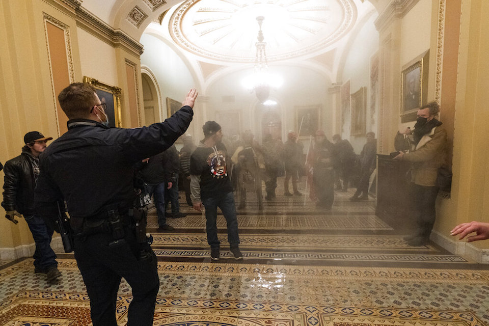 Smoke fills the walkway outside the Senate Chamber as violent rioters loyal to President Donald Trump are confronted by U.S. Capitol Police officers inside the Capitol in Washington, Jan. 6, 2021. New details from the deadly riot of Jan. 6 are contained in a previously undisclosed document prepared by the Pentagon for internal use that was obtained by the Associated Press and vetted by current and former government officials. (AP Photo/Manuel Balce Ceneta, File)