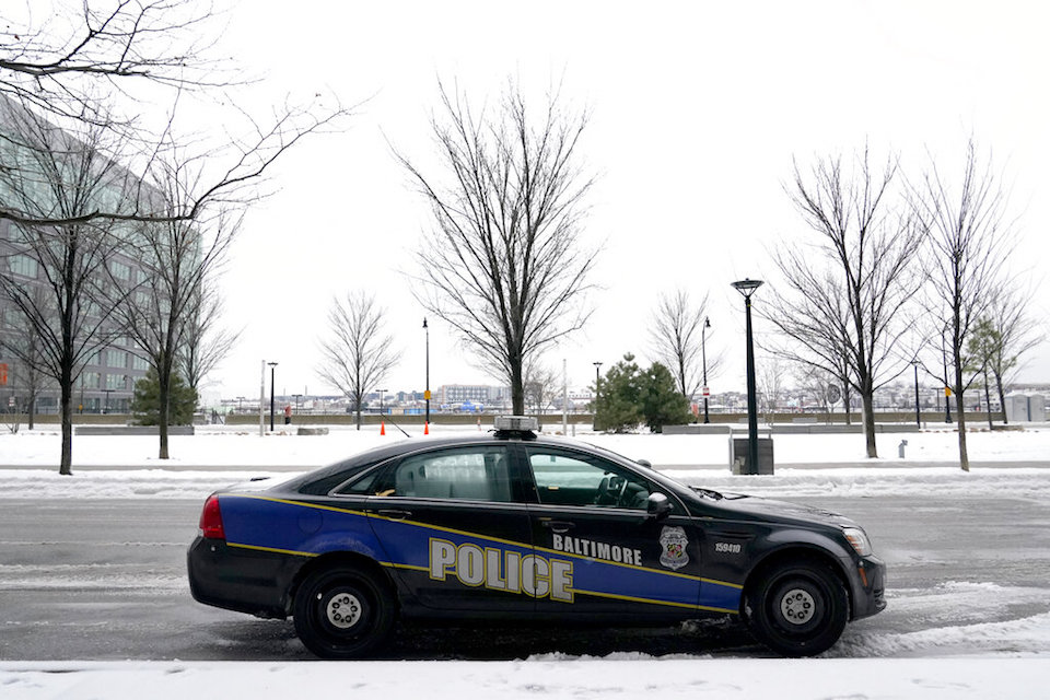 A Baltimore police cruiser is seen parked near a building while officers check on a call Thursday, Feb. 18, 2021. A comprehensive package of police reform measures cleared the Maryland General Assembly on Wednesday, April 7, 2021 including repeal of police job protections long cited as a barricade to accountability. (AP Photo/Julio Cortez, File)