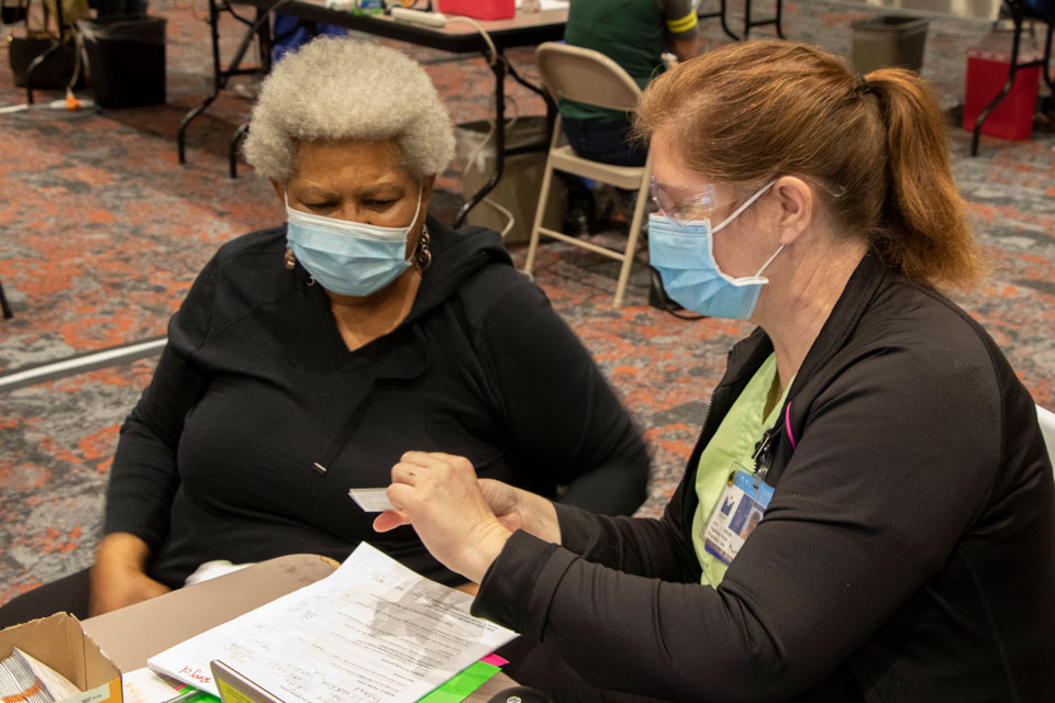 All4Oregon health system clinic worker screens patient at the Oregon Convention Center. (Photo/OHA)