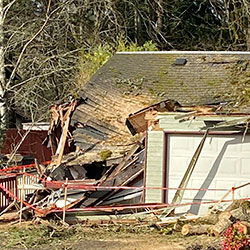 In this photo provided by Amber Moore, damage to a house from a downed tree is seen in Lake Oswego, Ore., on Wednesday, Feb. 17, 2021. More than 150,000 customers remain without power in the greater Portland, Ore., region nearly a week after a massive ice storm downed power lines and sent trees crashing onto houses and blocked roads. More than 300,000 customers lost power at the peak of the outage and there is no estimate for when full power will be restored. (Amber Moore via AP)
