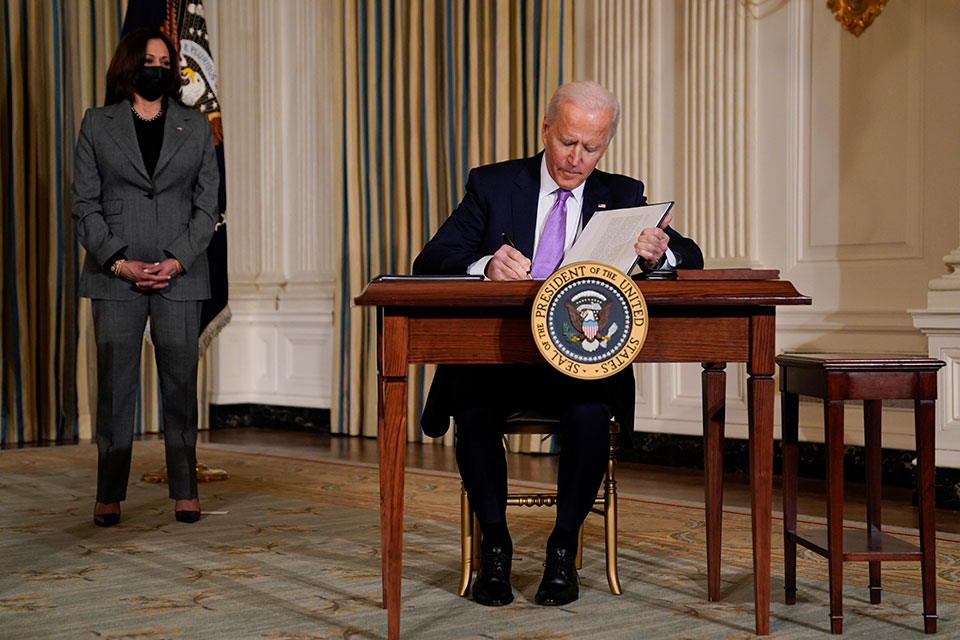 President Joe Biden signs executive orders in the State Dining Room of the White House, Tuesday, Jan. 26, 2021, in Washington. Vice President Kamala Harris listens at left. (AP Photo/Evan Vucci)