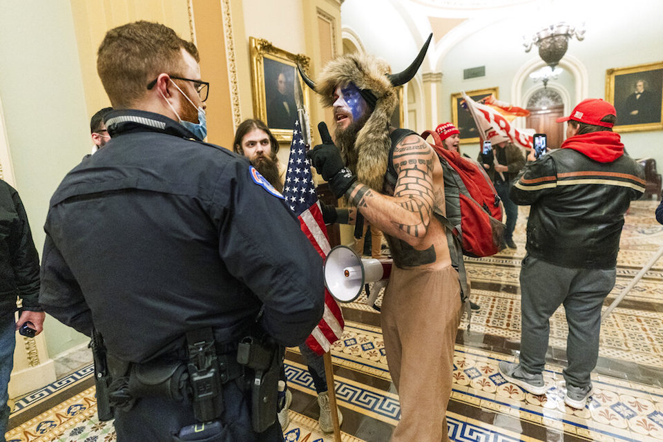 Supporters of President Donald Trump are confronted by U.S. Capitol Police officers outside the Senate Chamber inside the Capitol in Washington, Jan. 6, 2021. An Arizona man seen in photos and video of the mob wearing a fur hat with horns was also charged Saturday in Wednesday's chaos. Jacob Anthony Chansley, who also goes by the name Jake Angeli, was taken into custody Saturday, Jan. 9. (AP Photo/Manuel Balce Ceneta, File)
