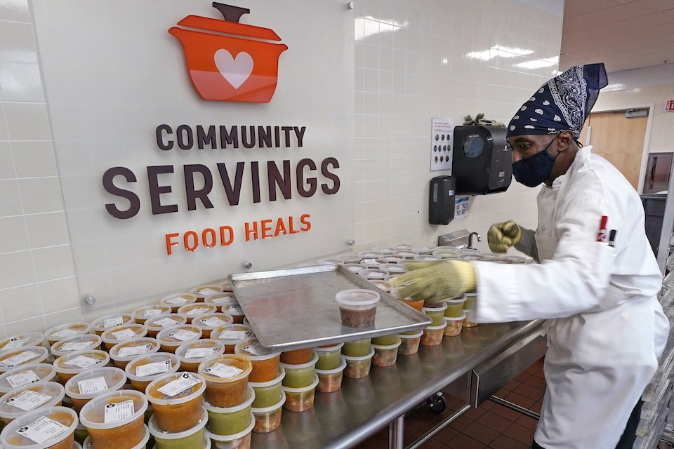Chef Jermaine Wall stacks containers of soups at Community Servings, which prepares and delivers scratch-made, medically tailored meals to individuals and families living with critical and chronic illnesses, Tuesday, Jan. 12, 2021, in the Jamaica Plain neighborhood of Boston. Food is a growing focus for insurers as they look to improve the health of the people they cover and cut costs. Insurers first started covering Community Servings meals about five years ago, and CEO David Waters says they now cover close to 40 percent. (AP Photo/Charles Krupa)