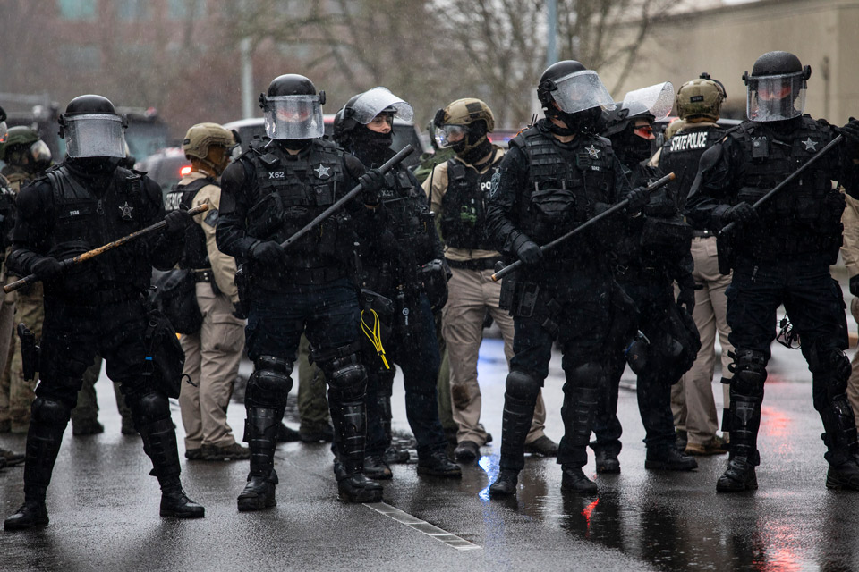 Oregon riot police stand at the scene of a protest at the Capitol on Wednesday, Jan. 6, 2021 in Salem, Ore. Thousands of President Donald Trump's supporters caused violence and chaos in Washington while Congress attempted to vote to certify that President-elect Joe Biden won the election. (AP Photo/Paula Bronstein)