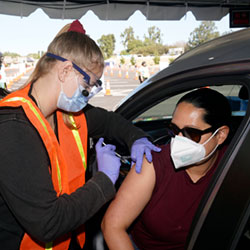 In this March 2, 2021, file photo, Vanessa Guerra, at right, a special education teacher at Grant Elementary School in Hollywood, receives a shot of the Moderna COVID-19 vaccine from nurse Kelly Mendoza at a site for employees of the Los Angeles school district in the parking lot of SOFI Stadium in Inglewood, Calif. Cities and states are rapidly expanding access to vaccines as the nation races to head off a resurgence in coronavirus infections and reopen schools and businesses battered by the pandemic. (AP Photo/Marcio Jose Sanchez, File)
