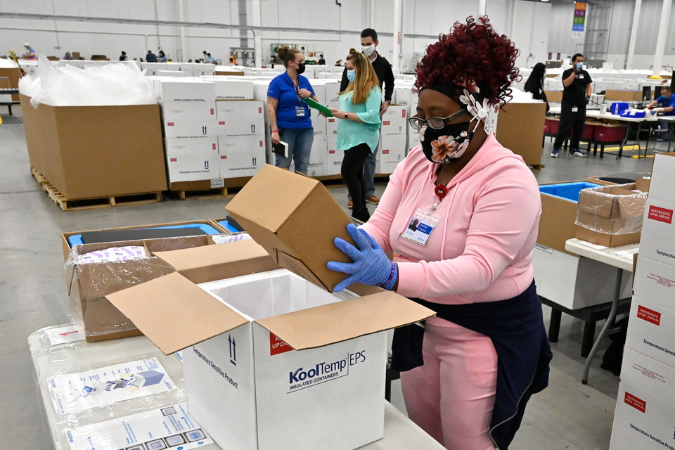 An employee with the McKesson Corporation packs a box of the Johnson and Johnson COVID-19 vaccine into a cooler for shipping from their facility in Shepherdsville, Ky., Monday, March 1, 2021. (AP Photo/Timothy D. Easley, Pool)