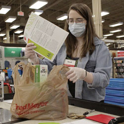 Sara Plush, an employee of the grocery chain Fred Meyer, adds a sheet with information about how to get a COVID-19 vaccine to groceries ordered by a homebound senior citizen in Portland, Ore., through the nonprofit group Store to Door on Feb. 25, 2021.