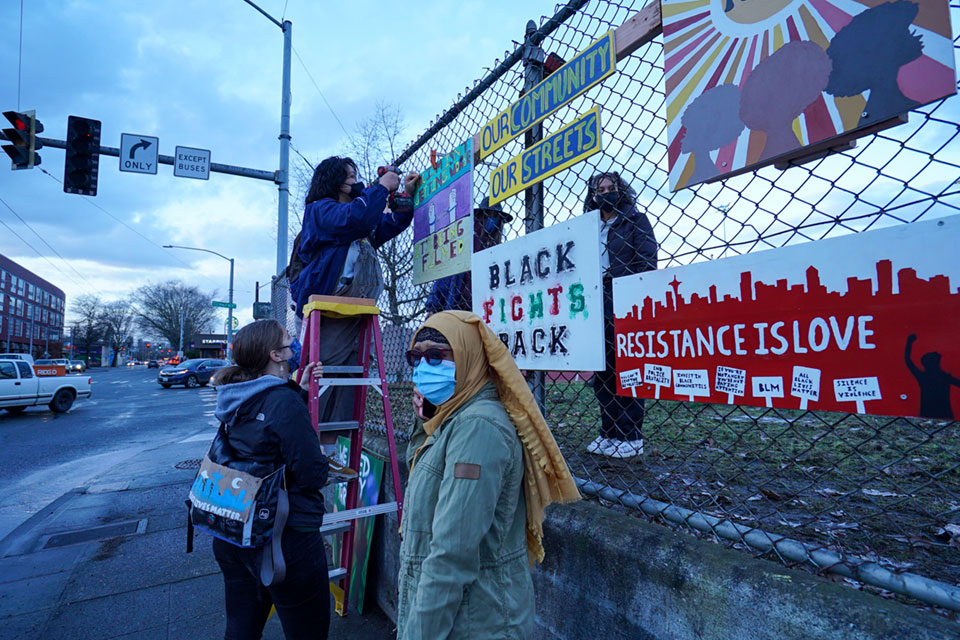 Members of Franklin High School's Art of Resistance and Resilience Club attached their new project to the fence that separates the school track and football field from Rainier Avenue on Friday February 26. The signs were created in reaction to the vandalism of a mural the club created in 2018, honoring the Seattle Chapter of the Black panthers that also hangs on the fence. The students met occasionally through zoom and were able to pick up the supplies they needed at the school and then work on their individual signs in the safety of their own homes.