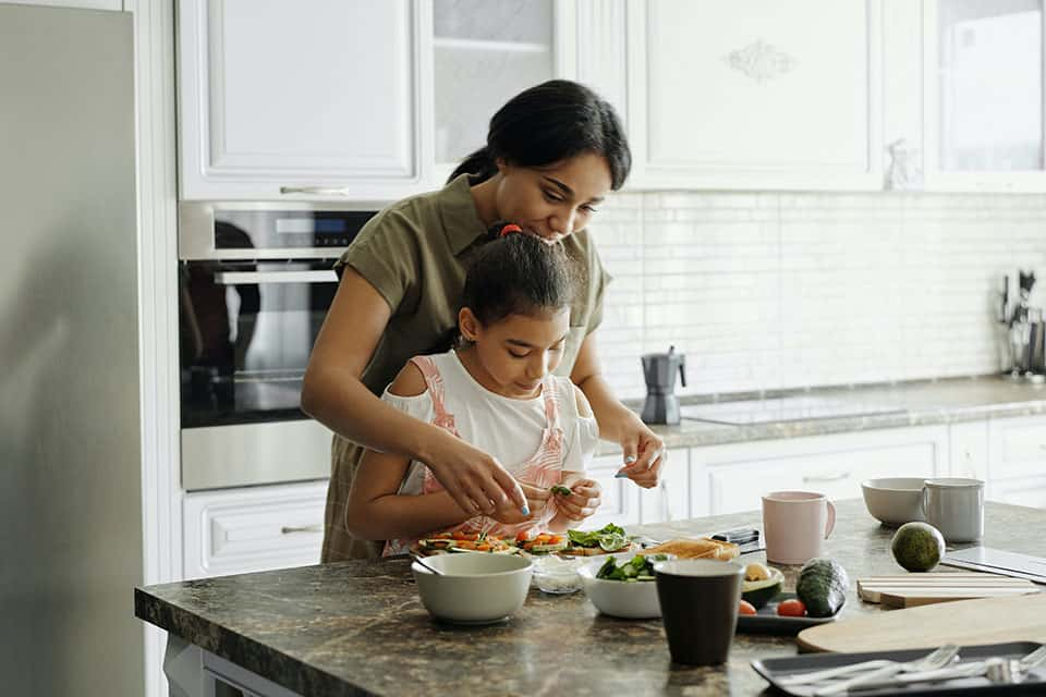Mother and daughter preparing a meal