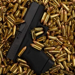 Black handgun in a bed of bullets