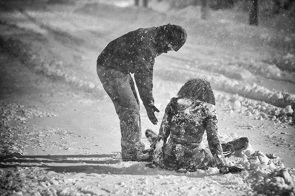 Man helping woman up in a blizzard