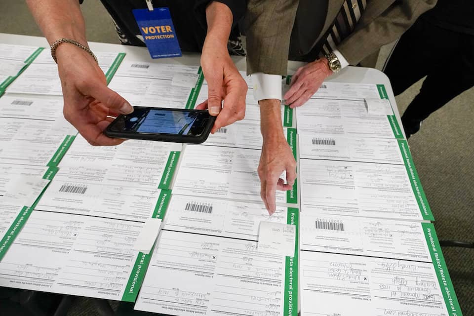 A canvas observer photographs Lehigh County provisional ballots as vote counting in the general election continues in Allentown, Pa., Nov. 6, 2020. President Donald Trump's campaign filed a number of lawsuits across six battleground states this month as he tried to upend the 2020 election. Judges uniformly rejected his claims of vote fraud. The latest case ended Saturday, Nov. 21, when a federal judge in Pennsylvania said Trump lawyer Rudy Giuliani presented only 'speculative accusations' that brought to mind 'Frankenstein's Monster.' (AP Photo/Mary Altaffer, File)