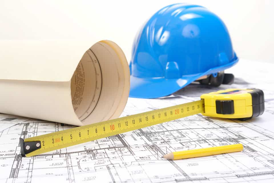 hard hat, measuring tape and blueprints