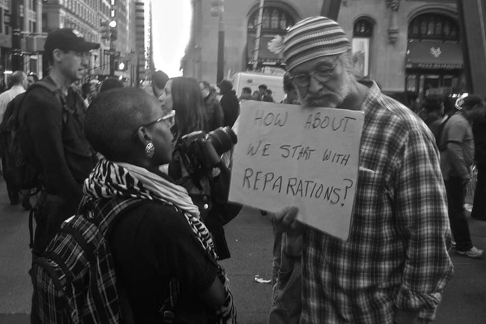 reparations man with sign