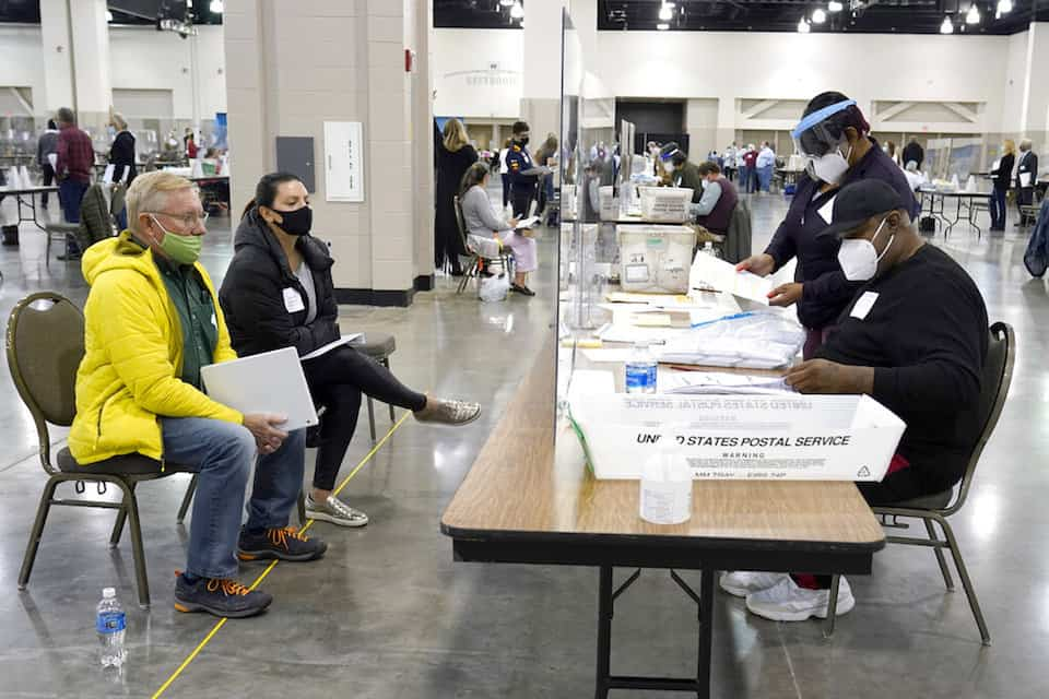 Election workers, right, verify ballots as recount observers, left, watch during a Milwaukee hand recount of presidential votes at the Wisconsin Center, Friday, Nov. 20, 2020, in Milwaukee. Wisconsin finished a partial recount of its presidential results on Sunday, Nov. 29, 2020 confirming Democrat Joe Biden's victory over President Donald Trump in the key battleground state. Trump vowed to challenge the outcome in court. (AP Photo/Nam Y. Huh)